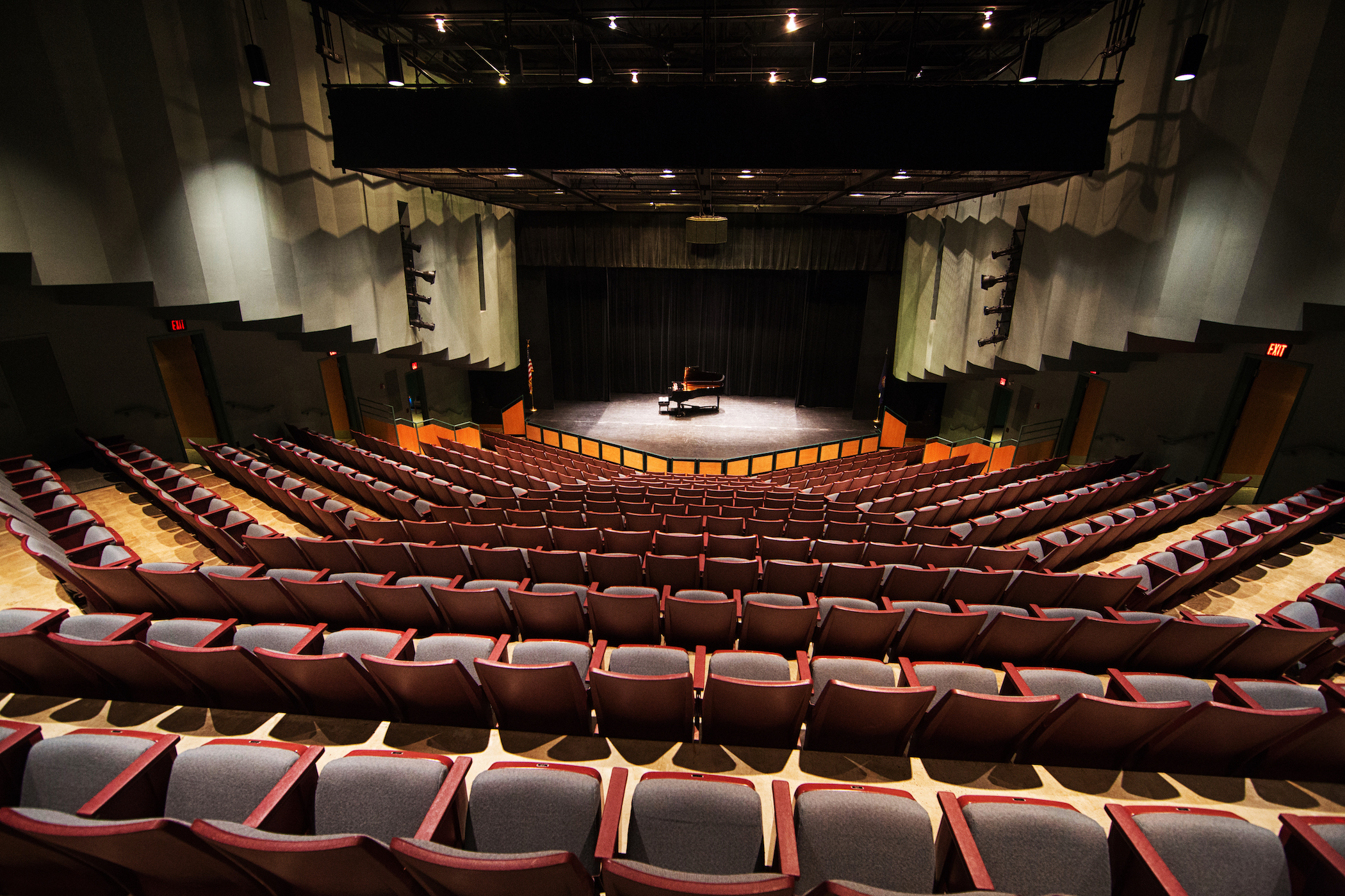 Picture of theatre seats  in Dickinson Theater looking downward at a stage with a grand piano